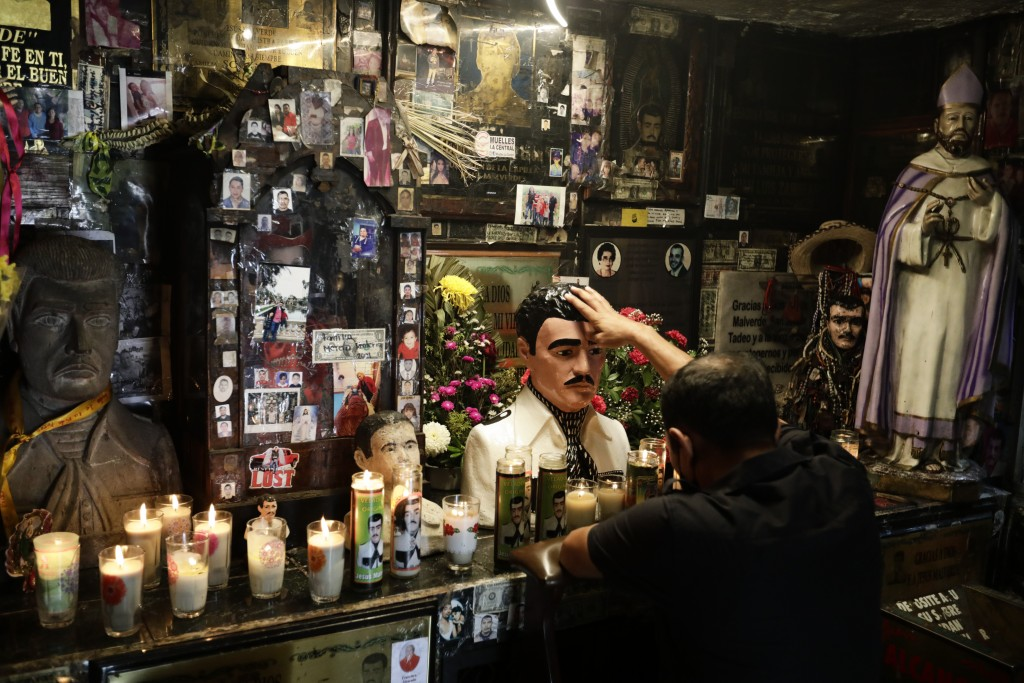 A man touches a statue of Jesus Malverde inside the shrine dedicated to the patron saint of drug dealers in Culiacan, Sinaloa state, Mexico, Thursday,...