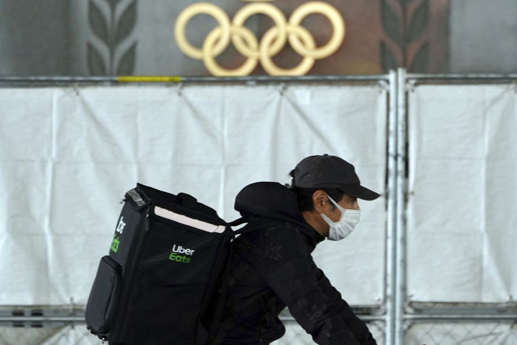 An Uber Eats delivery person carries items near the Japan National Stadium, where opening ceremony and other events are planned for postponed Tokyo 20...