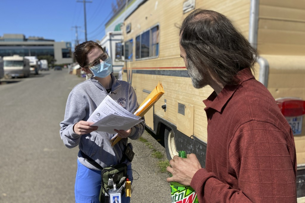 Moira Andrews, a street outreach nurse for Neighborcare Health, speaks with Shane Pisson, 48, who lives in an encampment in the Georgetown neighborhoo...