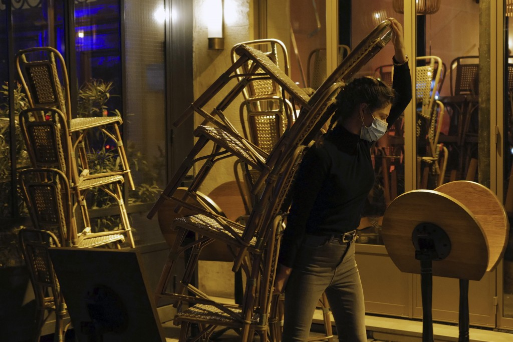 FILE - In this Sept. 28, 2020 file photo, a waiter carries chairs to close a bar terrace in Paris. France is expected Thursday April 15, 2021, to pass...