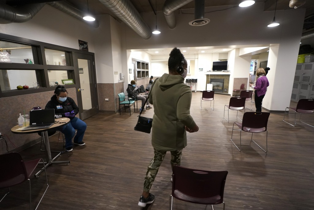 Cidney Oliver, center, walks through an area being used for a COVID-19 vaccination clinic Wednesday, April 7, 2021, at a YWCA shelter for women lackin...
