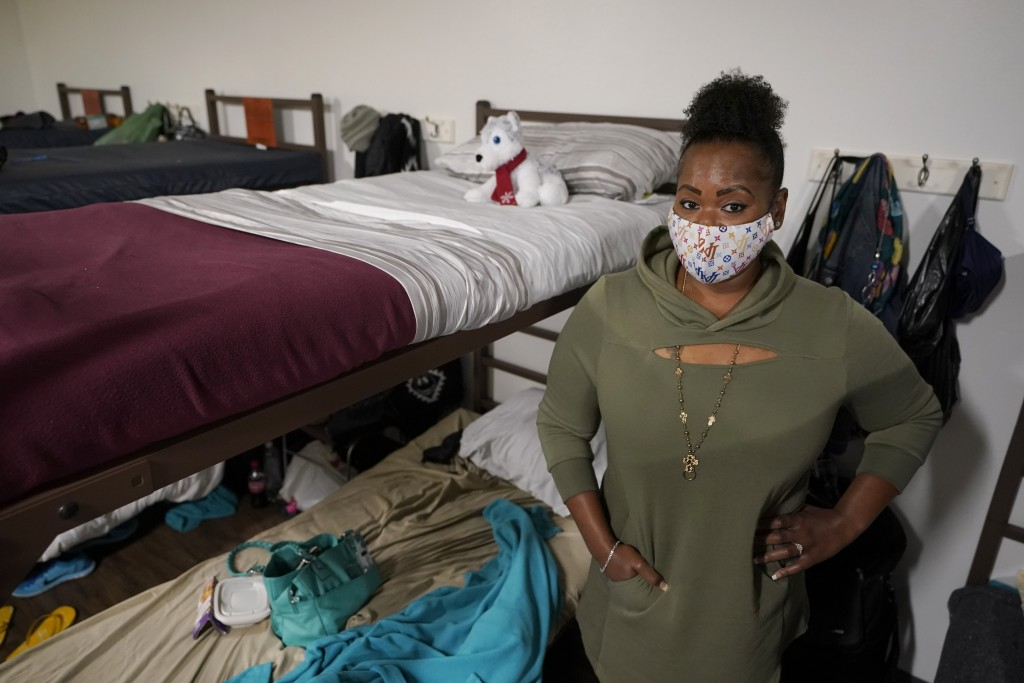 Cidney Oliver poses for a photo, Wednesday, April 7, 2021, by the bunk she sleeps on at a YWCA shelter for women lacking housing in Seattle. Earlier i...