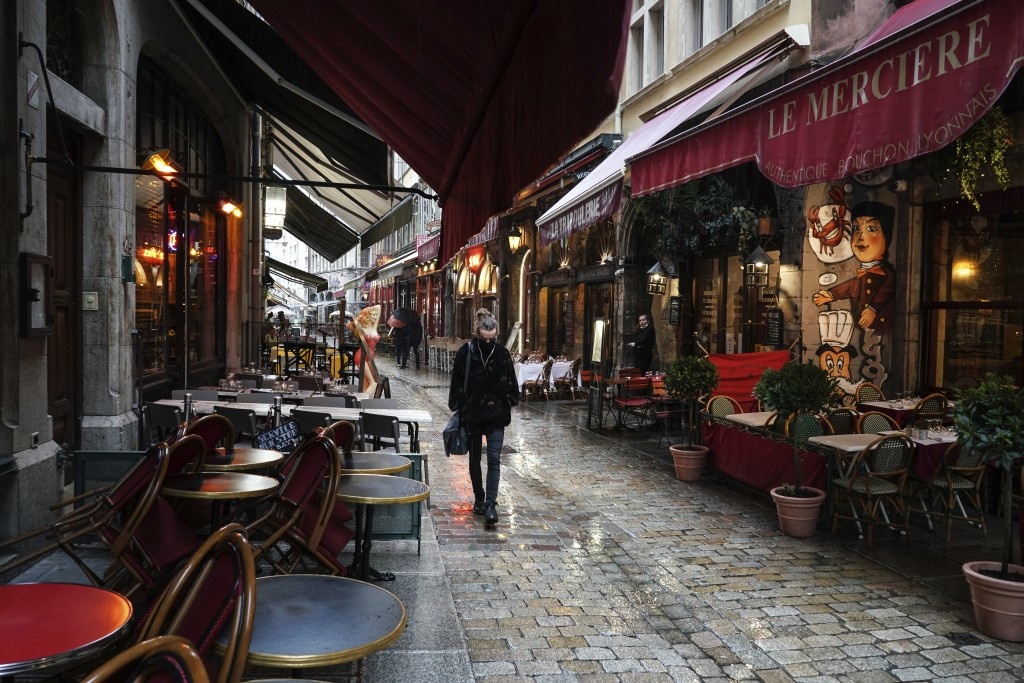 FILE - In this Oct. 2, 2020 file photo, a woman walks by empty restaurants in the center of Lyon, central France. France is expected Thursday April 15...