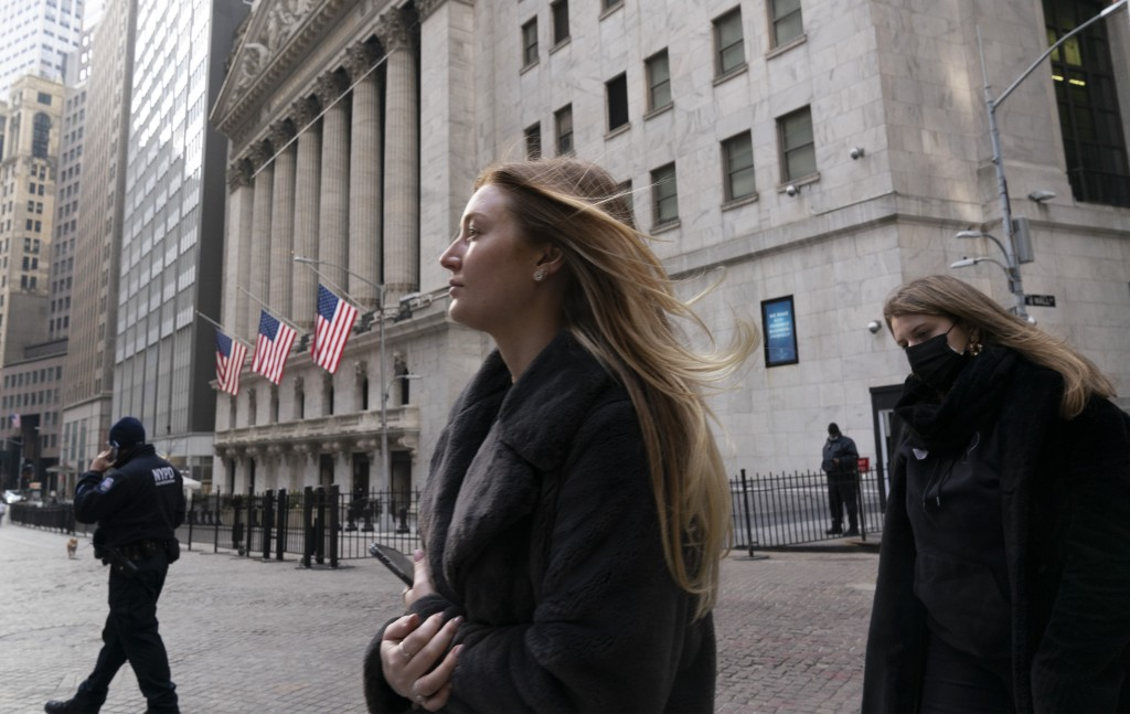 FILE - In this Jan. 13, 2021 file photo, people walk by the New York Stock Exchange. Stocks are opening higher on Wall Street as traders welcome some ...