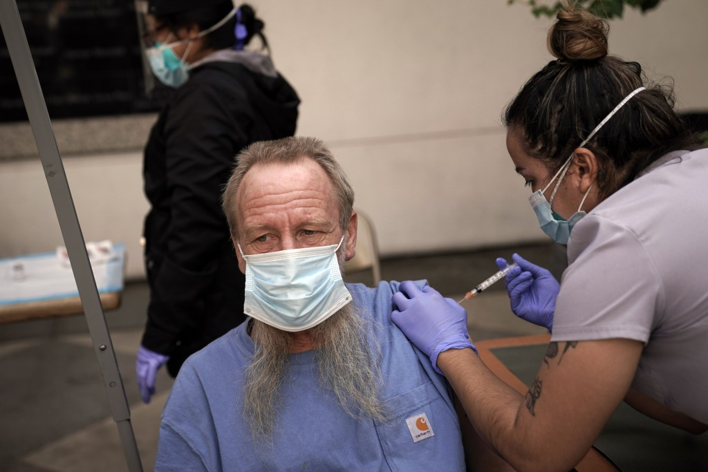 FILE - In this Feb. 3, 2021, file photo, EMT Rachel Bryant, right, administers a COVID-19 vaccine to a homeless man in the courtyard of the Midnight M...