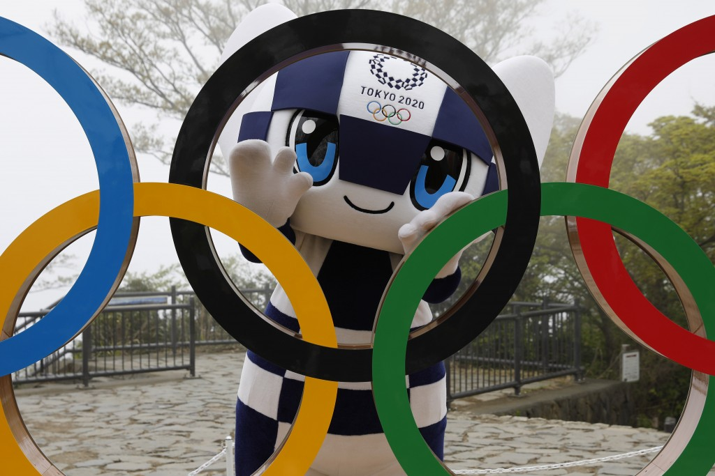 FILE - In this April 14, 2021, file photo, Tokyo 2020 Olympic Games mascot Miraitowa poses with a display of Olympic Symbol after an unveiling ceremon...