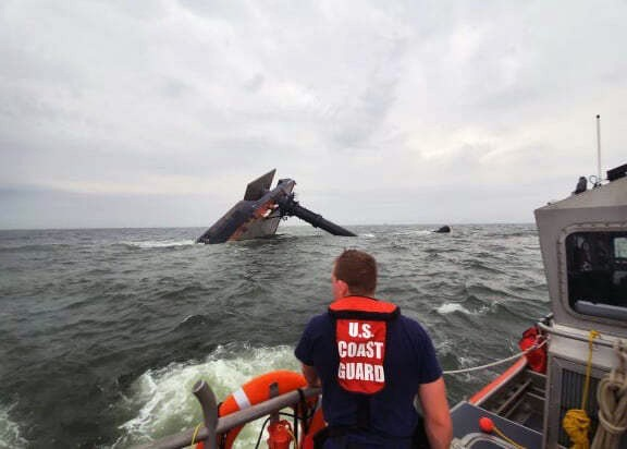 In this photo provided by the U.S. Coast Guard, A Coast Guard Station Grand Isle 45-foot Response Boat-medium boat crew member searches for survivors ...