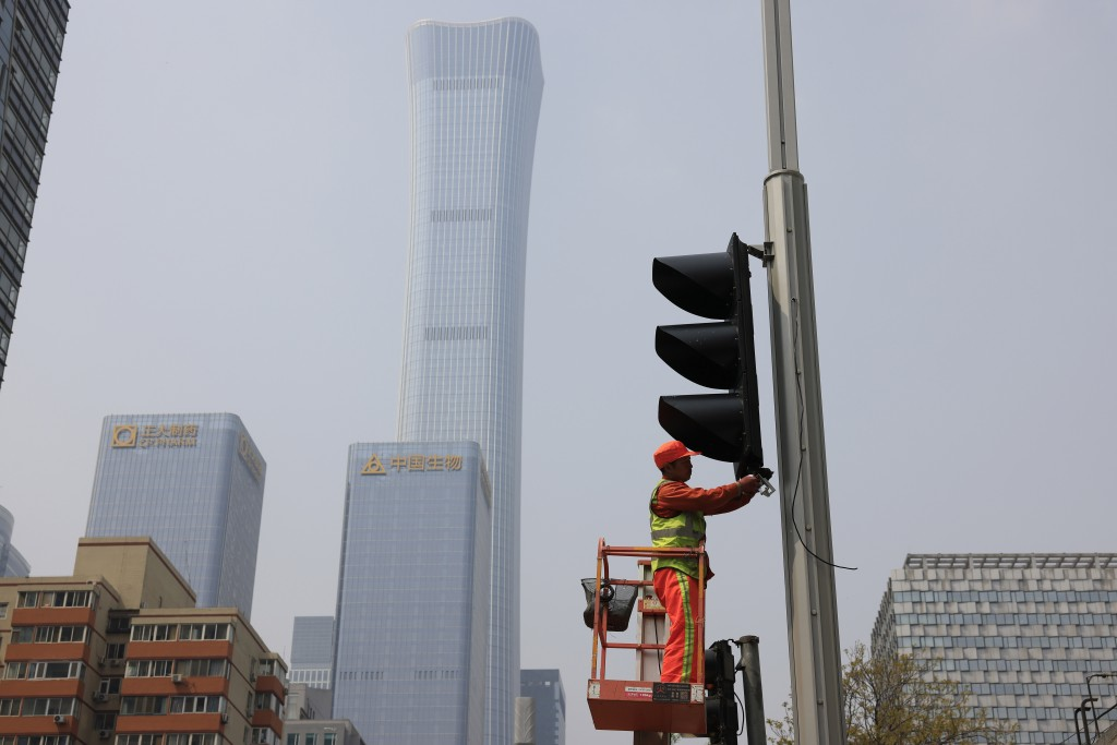 A worker installs new traffic lights at a junction in Beijing on Thursday, April 15, 2021. China's economic growth surged to 18.3% over a year earlier...