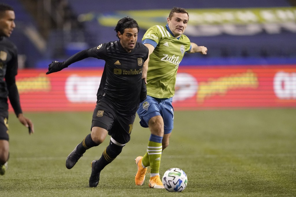FILE - Los Angeles FC forward Carlos Vela and Seattle Sounders forward Jordan Morris, right, vie for the ball during the second half of an MLS playoff...