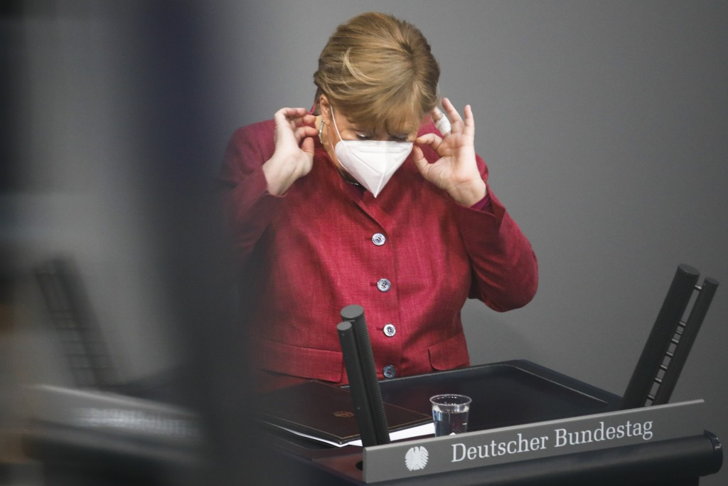 German Chancellor Angela Merkel adjust her face mask after her speech during a parliament session about a new law to battle the coronavirus pandemic a...