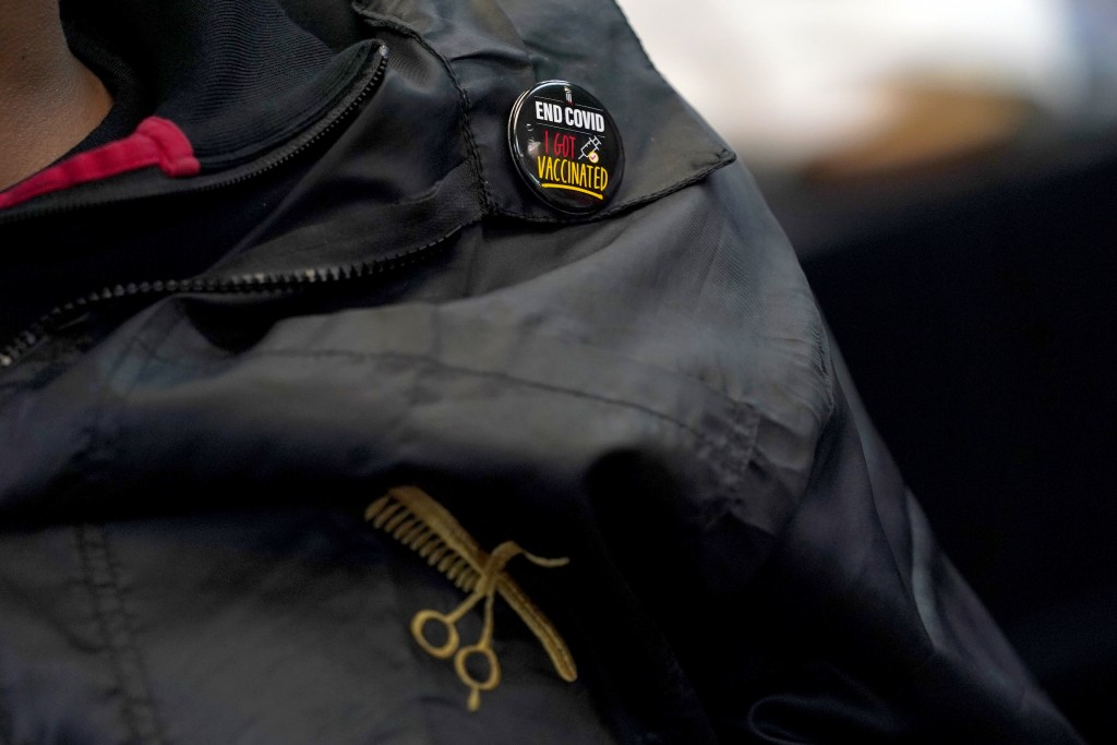 A pin is seen on the cutting coat of Mike Brown, a barber and health advocate, as he talks with colleagues and customers, Friday, April 9, 2021, in Hy...