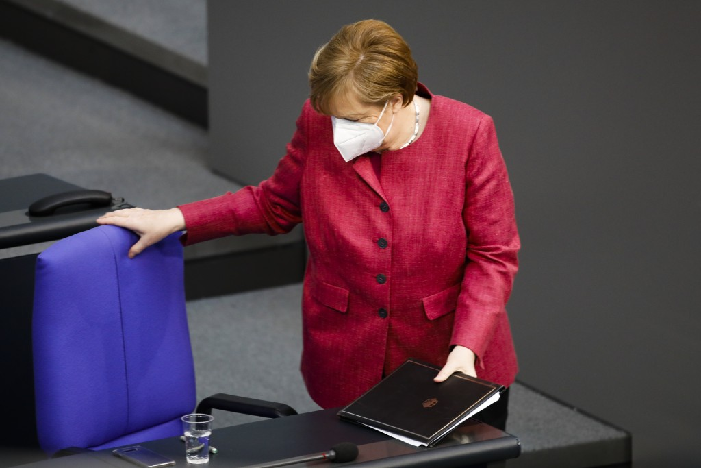 German Chancellor Angela Merkel takes her seat after her speech during a parliament session about a new law to battle the coronavirus pandemic at the ...