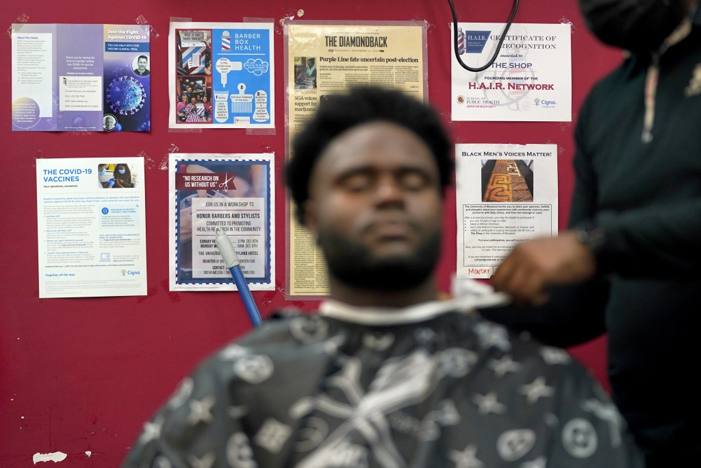 Health literature and a certificate are displayed on the wall as a patron gets a hair cut, Friday, April 9, 2021, in Hyattsville, Md. Barbers at The S...