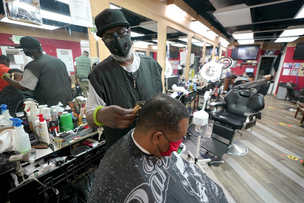 Wallace Wilson, top, cuts the hair of James McRae, Friday, April 9, 2021, in Hyattsville, Md. Wilson is a member of the Health Advocates In Reach & Re...