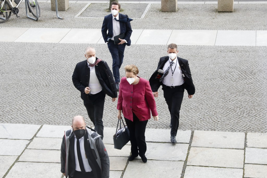 German Chancellor Angela Merkel, center, arrives for a parliament session about a new law to battle the coronavirus pandemic at the Bundestag at the R...