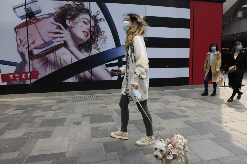 A woman walks her dog in a retail district in Beijing on Thursday, April 15, 2021. China's economic growth surged to 18.3% over a year earlier in the ...