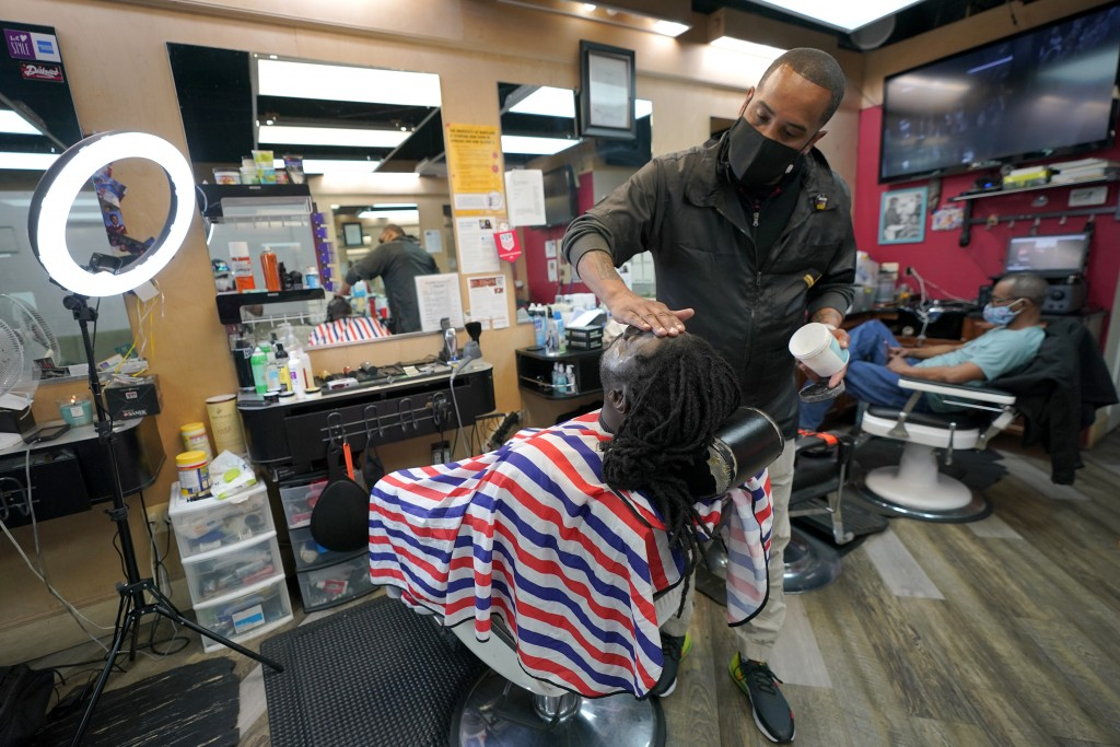 Mike Brown, right, a barber and health advocate, lines up the facial hair of Vyron Cox Jr., Friday, April 9, 2021, in Hyattsville, Md. Brown is a memb...