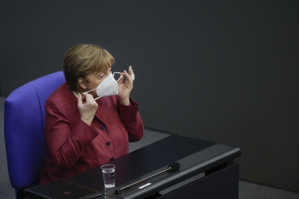 German Chancellor Angela Merkel adjusts her face mask as she arrives for a parliament session about a new law to battle the coronavirus pandemic at th...