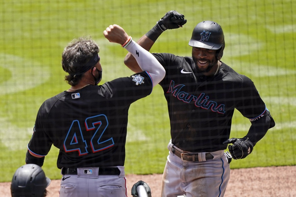 Miami Marlins' Starling Marte, right, celebrates with Miguel Rojas, left, after hitting a home run in the seventh inning of a baseball game against th...
