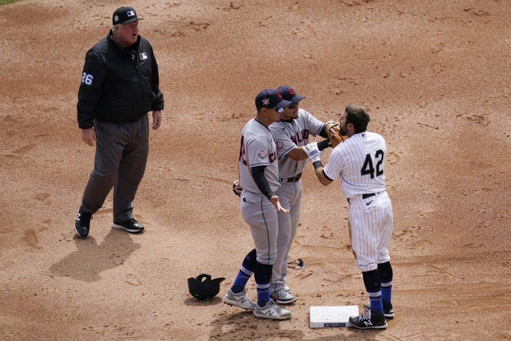 Cleveland Indians' second baseman Cesar Hernandez, left, and Indians shortstop Andres Gimenez, center, argue with Chicago White Sox's Adam Eaton at se...