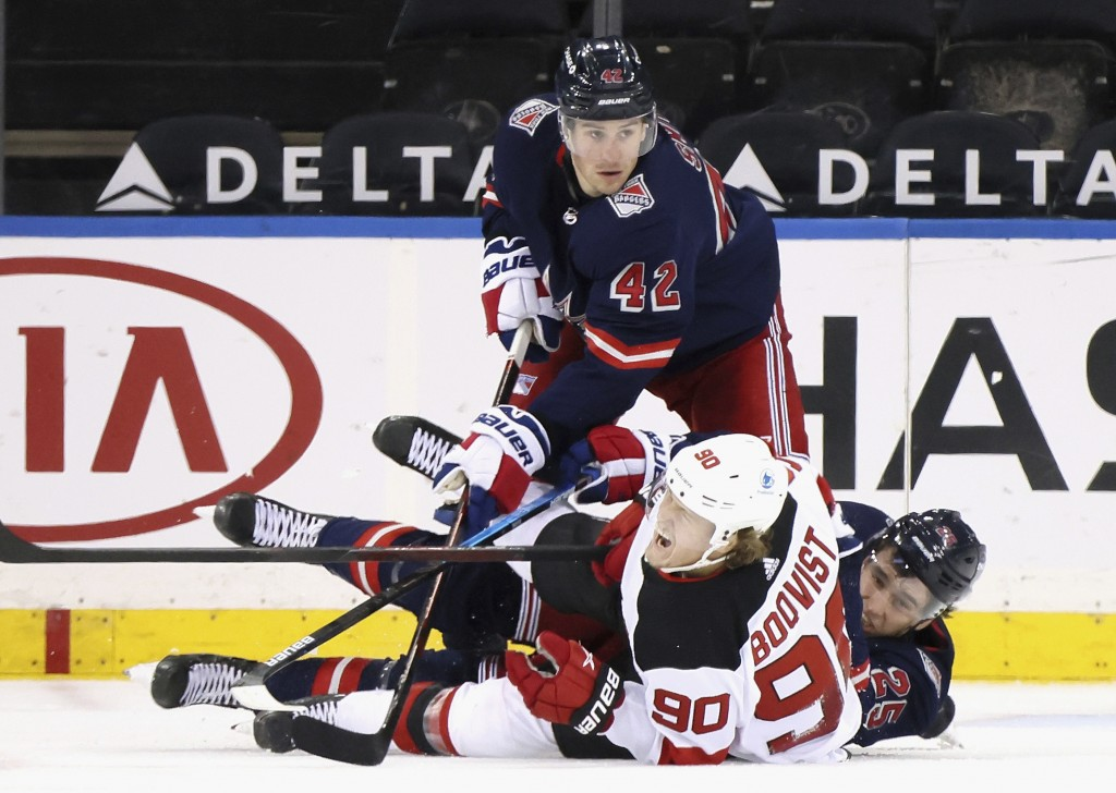 New York Rangers' Brendan Smith (42) and Libor Hajek (25) combine to check New Jersey Devils' Jesper Boqvist (90) during the second period of an NHL h...