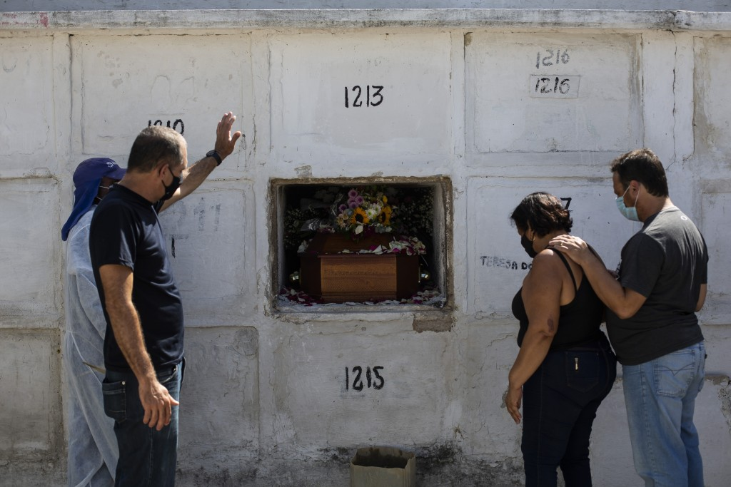 Carlos Alberto holds out his left arm during the burial service for his 41-year-old wife Aparecida de Freitas, who died from complications related to ...
