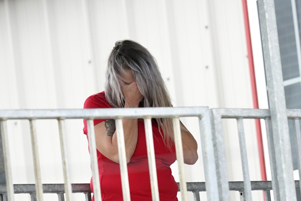 Marion Cuyler, fiancée of missing crew member Chaz Morales, talks on her cell phone at a fire station where family members of 12 people missing from a...