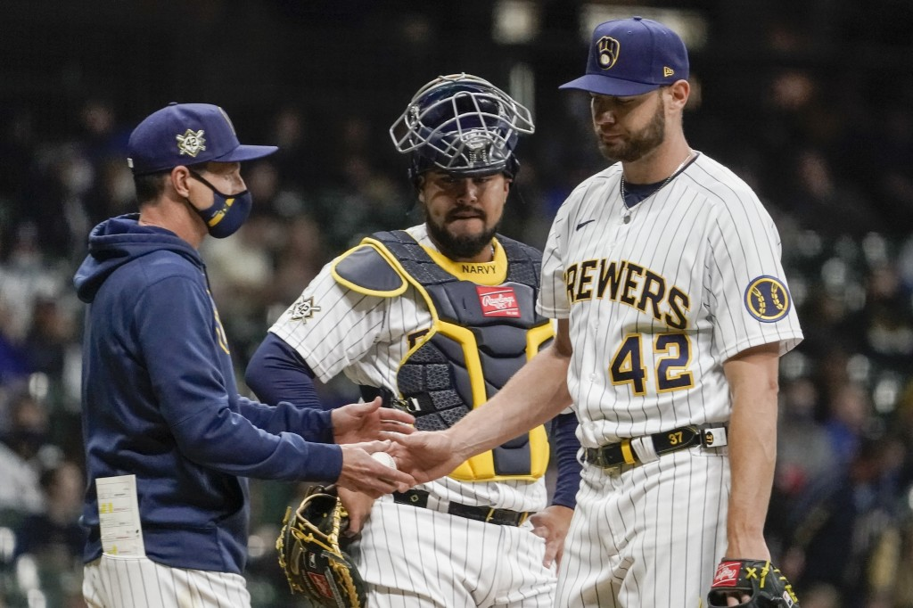 Milwaukee Brewers manager Craig Counsell take starting pitcher Adrian Houser out of the game during the fifth inning of a baseball game against the Pi...