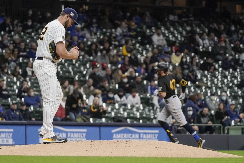 Milwaukee Brewers starting pitcher Adrian Houser reacts after giving up a home run to Pittsburgh Pirates' Colin Moran during the second inning of a ba...