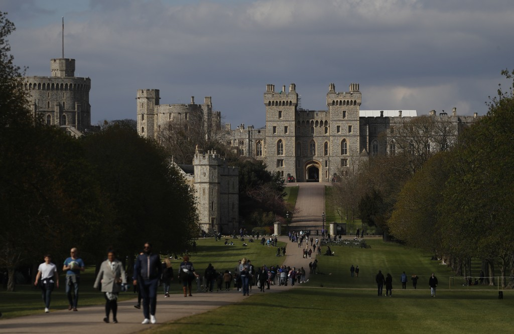 People walk along the Long Walk in front of Windsor Castle In Windsor, England, Friday, April 16, 2021. Prince Philip husband of Britain's Queen Eliza...