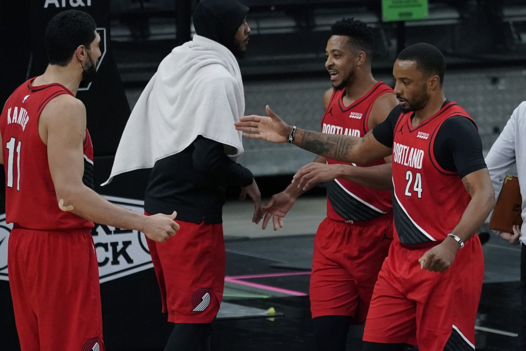 Portland Trail Blazers forward Norman Powell (24) and guard CJ McCollum, second from right, celebrate their win against the San Antonio Spurs with tea...