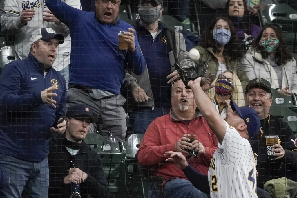 Fans watch as Milwaukee Brewers' Travis Shaw catches a foul ball hit by Pittsburgh Pirates' Gregory Polanco during the fourth inning of a baseball gam...