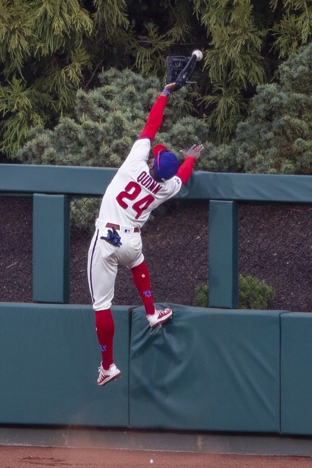 Philadelphia Phillies center fielder Roman Quinn goes over the fence trying to catch a home run by St. Louis Cardinals' Paul DeJong (11) during the th...