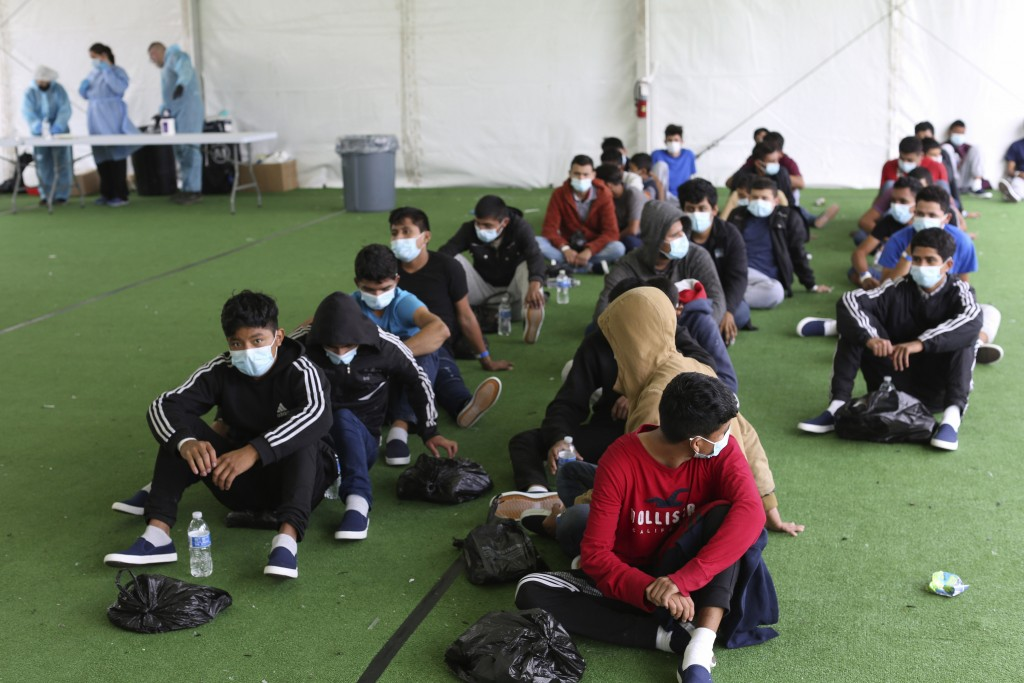 FILE - In this March 30, 2021, file photo, young migrants wait to be tested for COVID-19 at the Donna Department of Homeland Security holding facility...