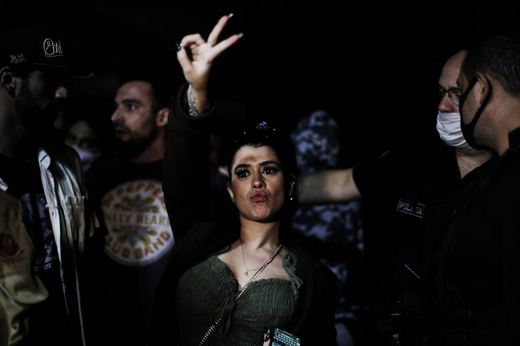 A woman flashes a V sign as police break up a social gathering during an operation against illegal and clandestine gatherings that authorities believe...