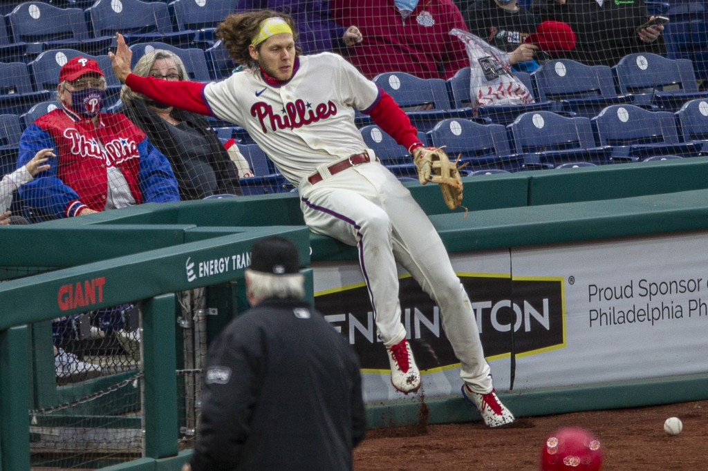 Philadelphia Phillies third baseman Alec Bohm (28) falls into the nets trying to catch a foul ball from St. Louis Cardinals' Dylan Carlson (3) during ...