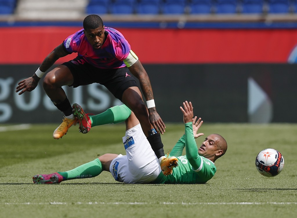 PSG's Presnel Kimpembe, left, leaps above Saint-Etienne's Wahbi Khazri as they compete for the ball during the French League One soccer match between ...