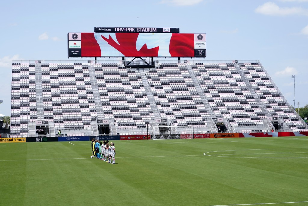 CF Montreal and Toronto FC players stand for the national anthem in a nearly empty DRV PNK Stadium during the first half of an MLS soccer match, Satur...