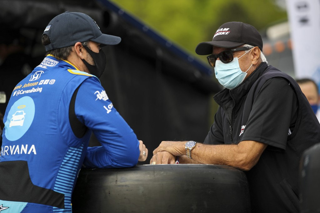 In this image provided by IndyCar, seven-time NASCAR champion Jimmie Johnson,left, speaks to four-time Indianapolis 500 winner Rick Mears before the f...
