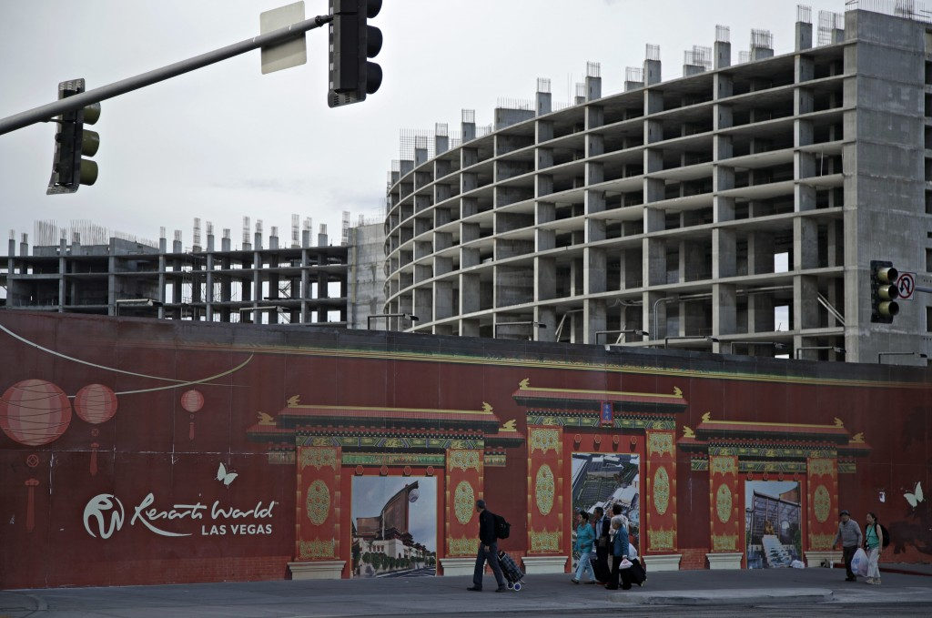 FILE - In this May 16, 2017, file photo, people walk by the Resorts World Las Vegas site in Las Vegas. On Monday, April 19, 2021, Resorts World Las Ve...