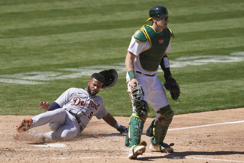 Detroit Tigers' Willi Castro, left, slides home to score behind Oakland Athletics catcher Sean Murphy during the sixth inning of a baseball game in Oa...
