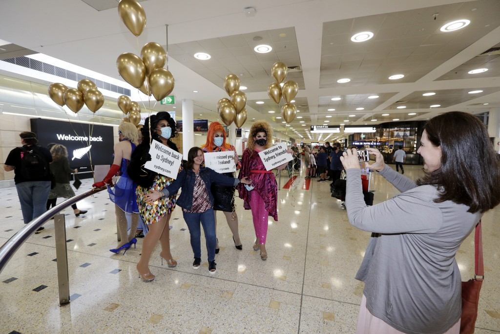 A passenger from New Zealand, center, poses with drag queens as they welcome her at Sydney Airport in Sydney, Australia, Monday, April 19, 2021, as th...