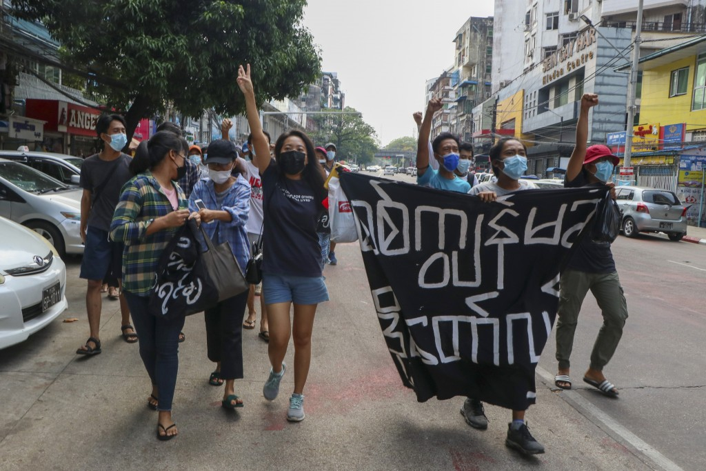 Anti-coup protesters shout slogan with a banner reading ''Carry on revolution! We do not accept as the military slave,'' in Kamayut township of Yangon...