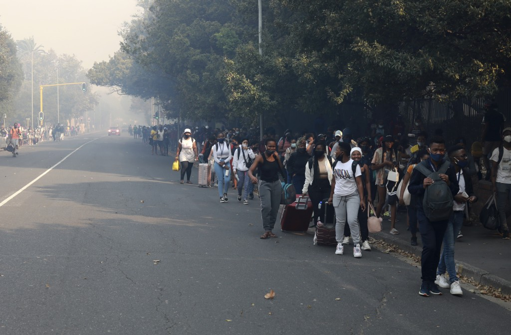 Students make their way after being evacuated from their residence at the University of Cape Town, South Africa, Sunday, April 18, 2021. A wildfire ra...