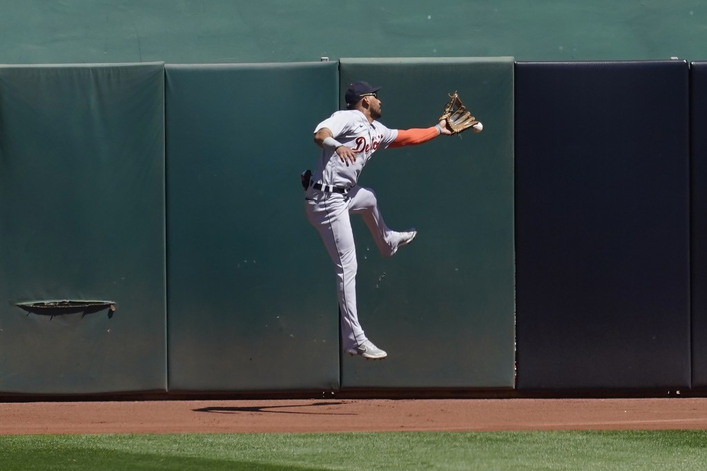 Detroit Tigers center fielder Victor Reyes cannot catch a run-scoring triple hit by Oakland Athletics' Ramon Laureano during the fourth inning of a ba...