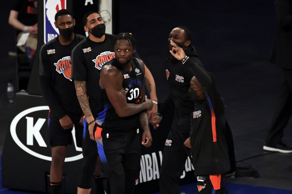 New York Knicks forward Julius Randle (30) reacts with teammates after making a 3-point basket during overtime of an NBA basketball game against the N...