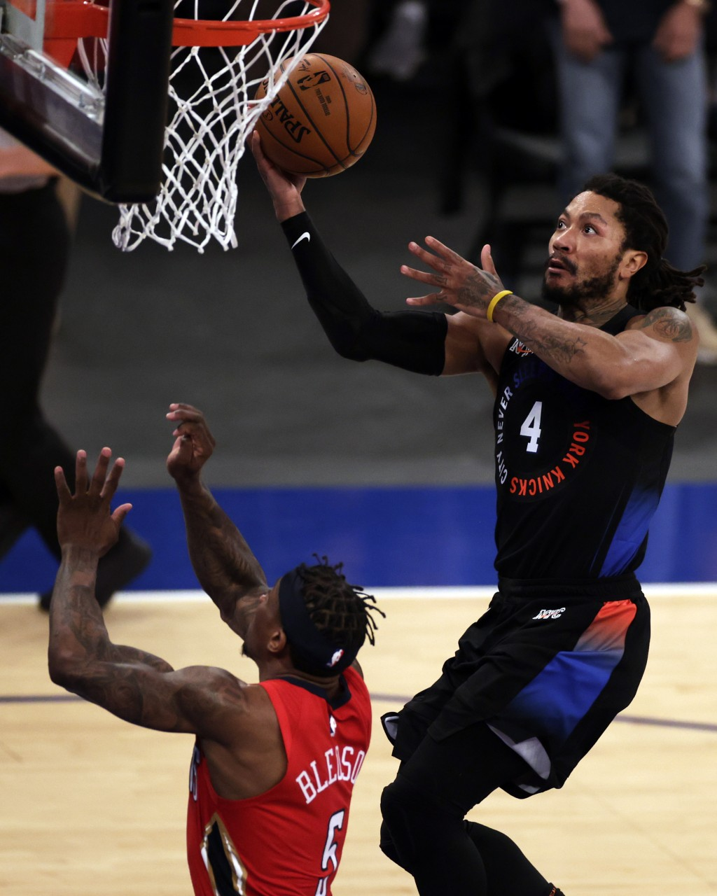 New York Knicks guard Derrick Rose, right, drives to the basket past New Orleans Pelicans guard Eric Bledsoe, left, during overtime of an NBA basketba...