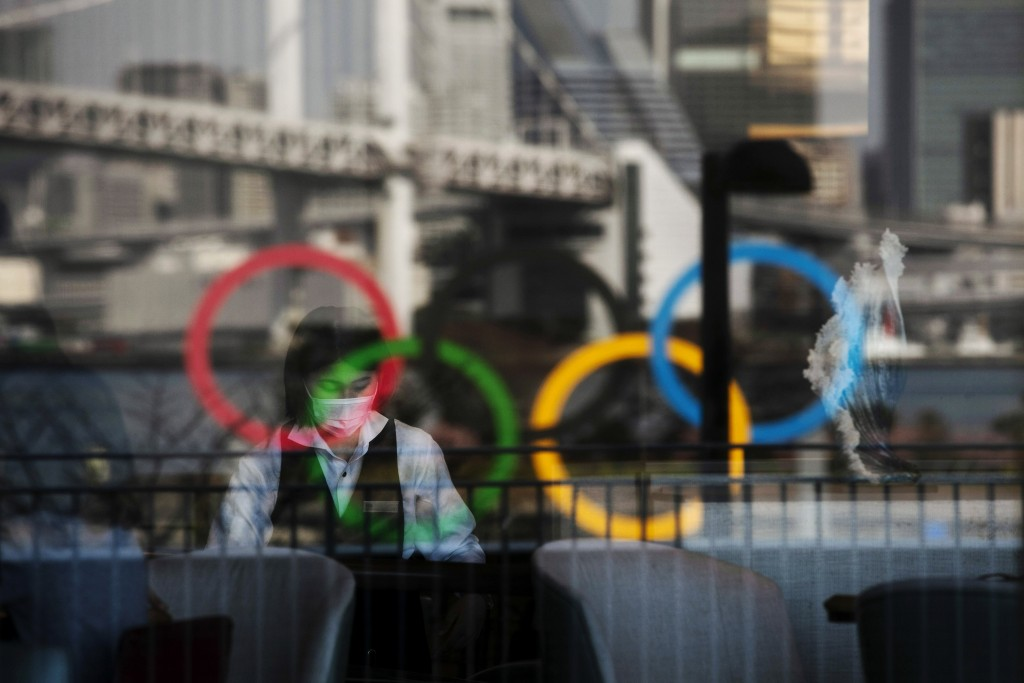FILE - In this Feb. 24, 2020, photo, the Olympics rings are reflected on the window of a hotel restaurant as a server with a mask sets up a table, in ...