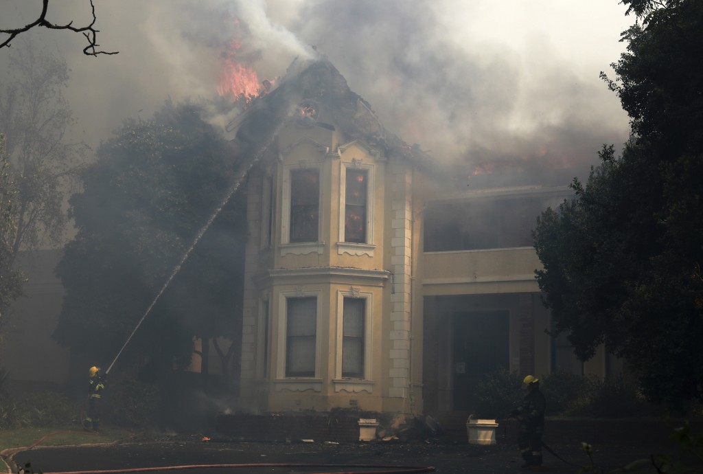 Firefighters douse a burning building at the University of Cape Town, South Africa, Sunday, April 18, 2021. A wildfire raging on the slopes of Table M...