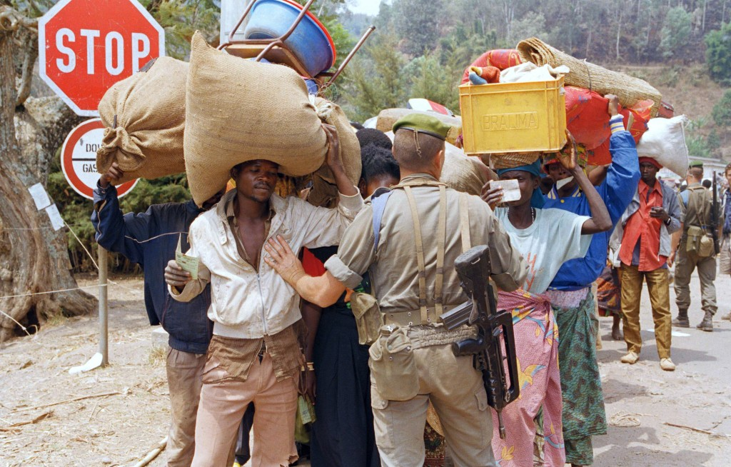 FILE - In this Aug. 15, 1994 file photo, a French soldier holds up a line of Rwandan refugees as they prepare to cross into Bukavu, in then Zaire on A...